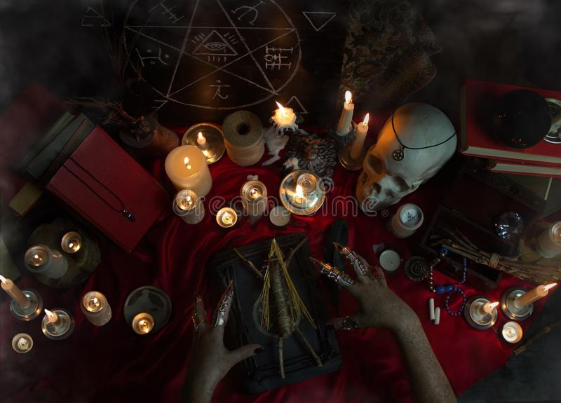Black magic ritual with Voodoo doll. Witchcraft composition with witch`s hands carrying out a ritual with Voodoo doll, candles, magic books, human skull, crystal royalty free stock photo