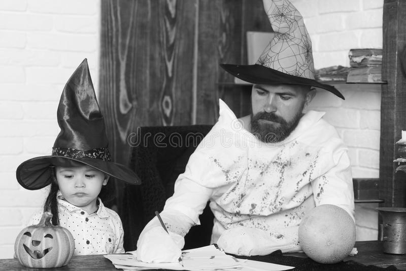 Witcher и маленький волшебник делают оформление хеллоуина Человек и ребенк с серьезными сторонами играют с тыквами стоковые фото