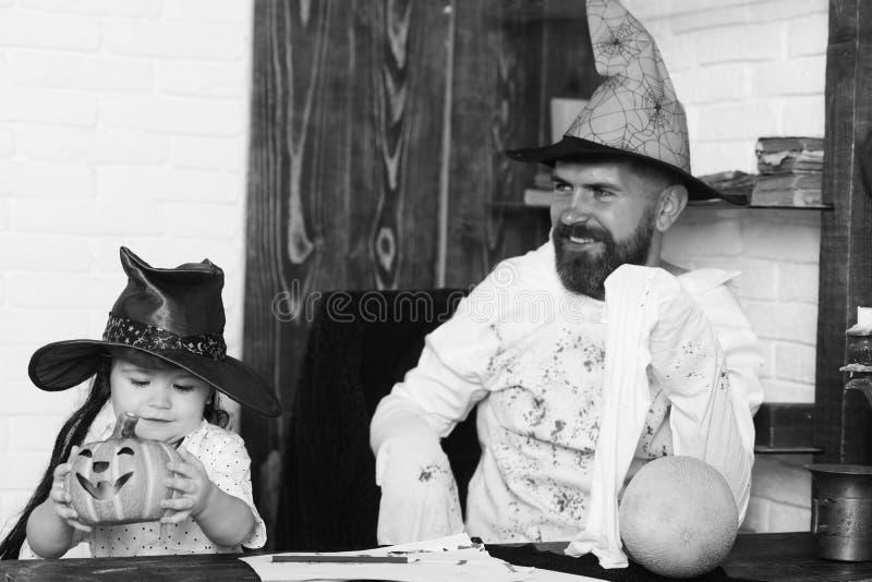 Witcher i mały magik robimy Halloweenowemu wystrojowi Mężczyzna i chłopiec na ściana z cegieł tle drewnianym i białym obraz royalty free