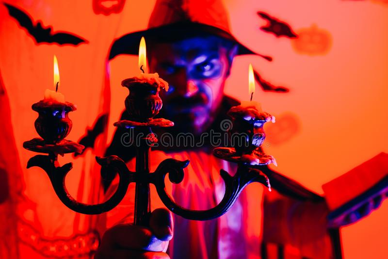 Witcher malvado con el pelo rojo y una barba en una capa negra que lee un libro de encantos Misterio y concepto del horror mago foto de archivo libre de regalías