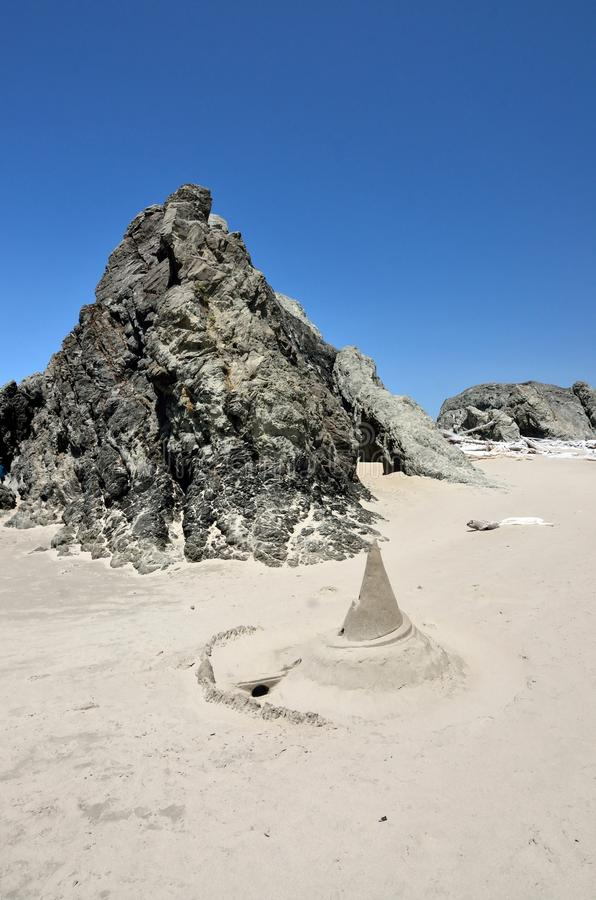 """Witches Hat"" Sand Castle In Front Of Rock On Beach royalty free stock photos"