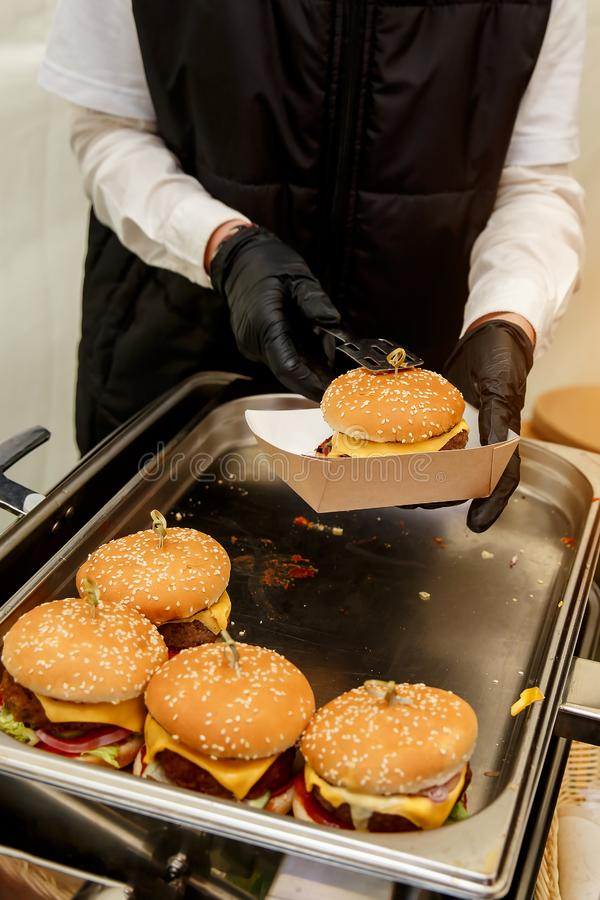 Witer in black gloves gives burger on event. Witer in black gloves gives burger on event stock photos