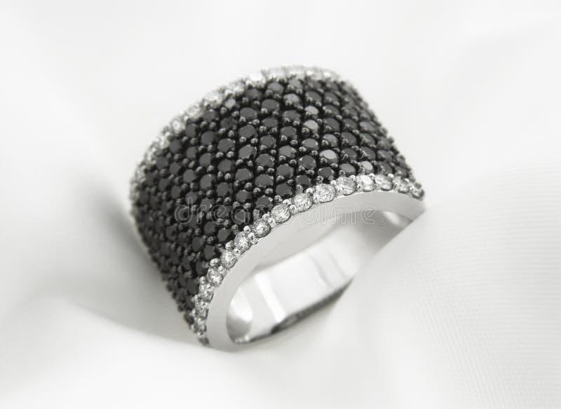 Witgoudring met zwart-witte diamanten op zachte achtergrond stock fotografie