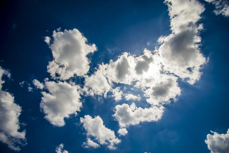 Withe clouds hiding the sun against a deep blue sky royalty free stock image