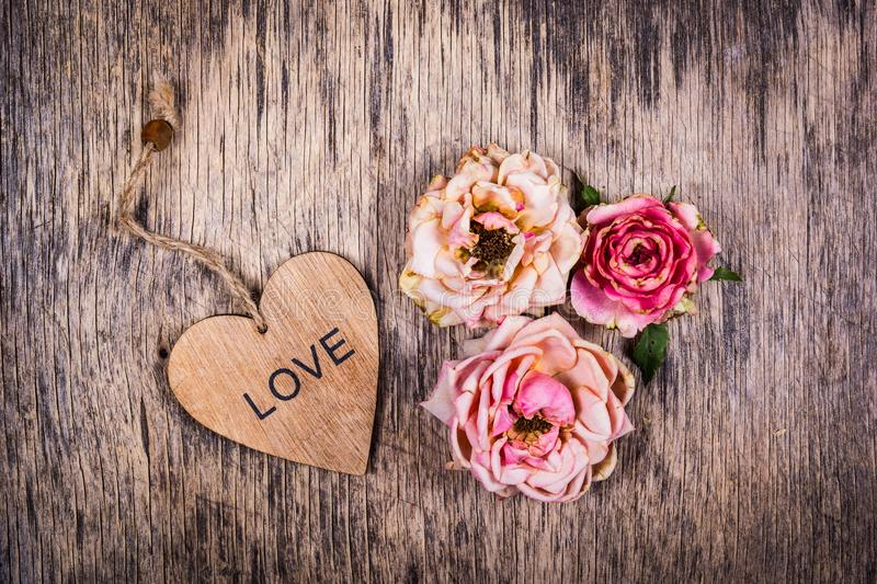 Withered roses and a wooden heart. Passed love. Dead flowers on an old wooden background. Withered roses and a wooden heart. Dead flowers on an old wooden royalty free stock photos