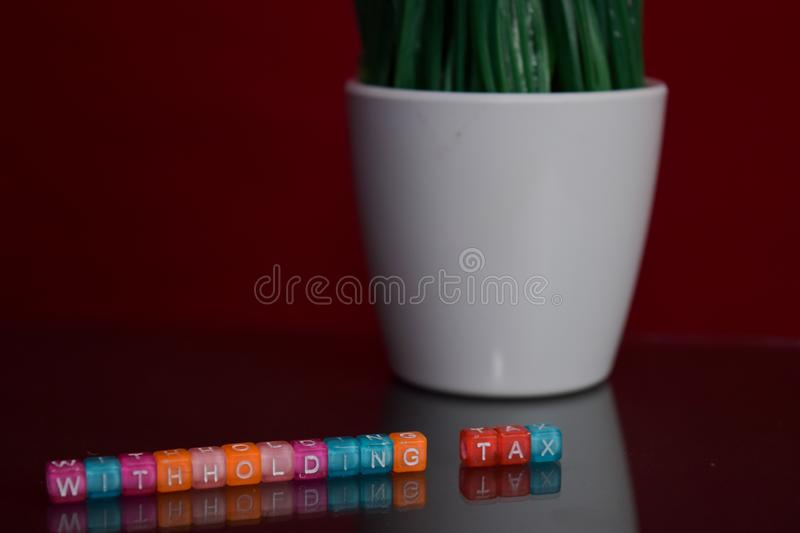 Withholding tax text at colorful wooden block on red background. Desk office and education concept stock photos