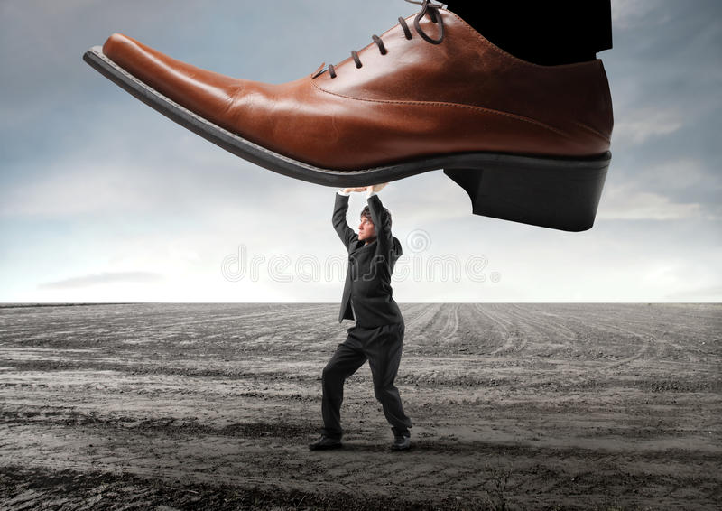 Withstand. Businessman withstanding a huge foot trying to squash him royalty free stock image