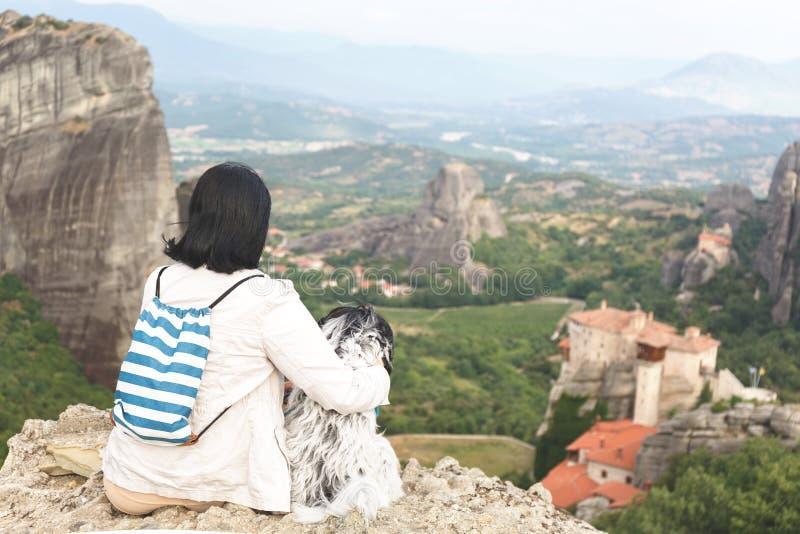 WithTibetan Terrierhund der Frau, der am Rand einer Klippe übersieht Meteora-Tal sitzt lizenzfreie stockfotografie