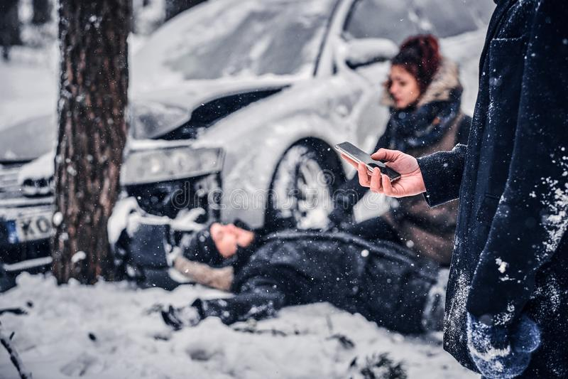 The witness of the accident keeps the phone and is going to call the rescue service. The car got into a skid and crashed into a tree on a snowy road royalty free stock images