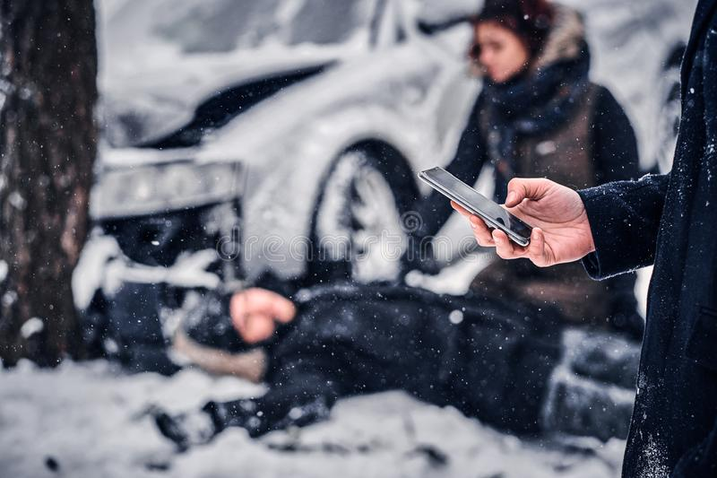 The witness of the accident keeps the phone and is going to call the rescue service. The car got into a skid and crashed into a tree on a snowy road royalty free stock photo