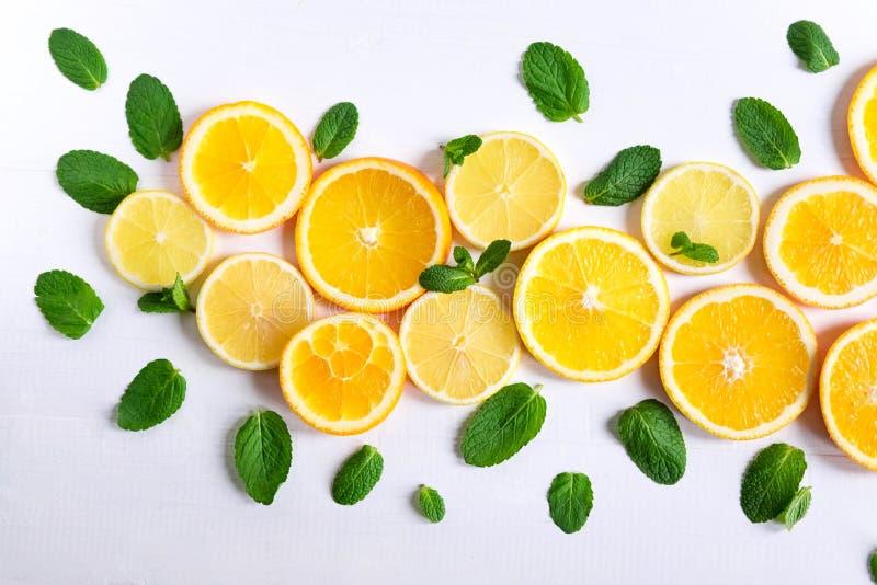 Witte achtergrond met citroen, oranje plakken en munt Concept met vers fruit Citroen, Sinaasappel, Munt Mening van hierboven royalty-vrije stock foto