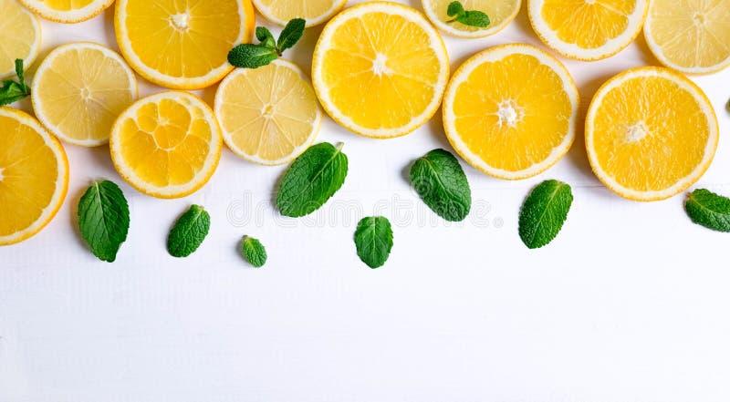 Witte achtergrond met citroen, oranje plakken en munt Concept met vers fruit Citroen, Sinaasappel, Munt Mening van hierboven stock foto's