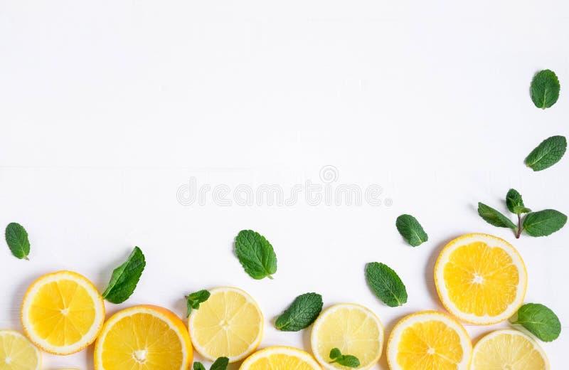 Witte achtergrond met citroen, oranje plakken en munt Concept met vers fruit Citroen, Sinaasappel, Munt Mening van hierboven stock afbeeldingen