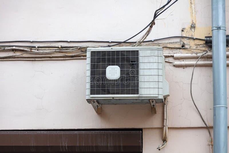 Witte airconditioning op de oude muur van het huis met de oude draden van mededeling over de plastic rioolbuis boven het venster stock afbeeldingen