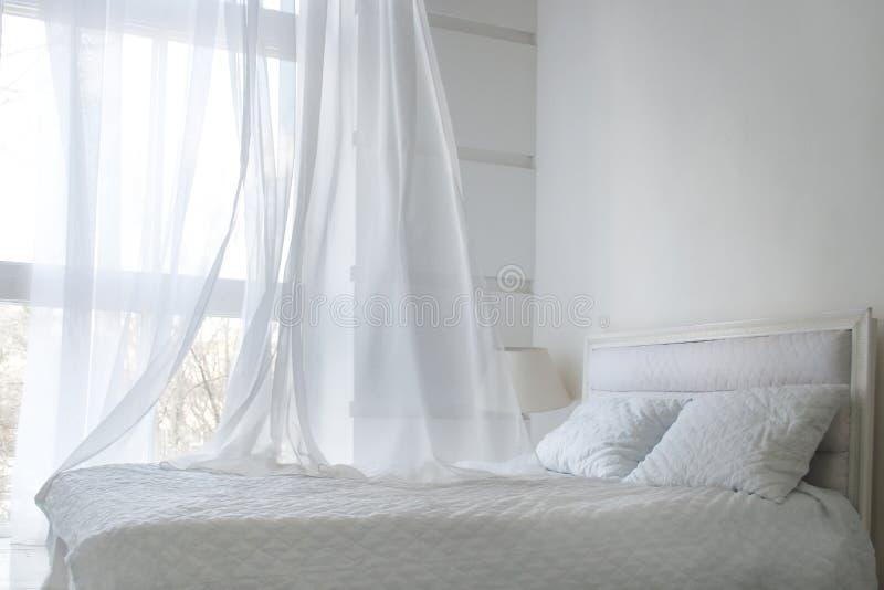 Witte als thema gehade bedbladen en wit gordijn in de ochtend, slaapkamerbinnenland stock foto