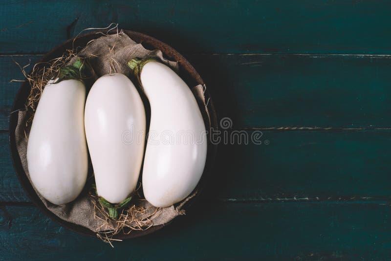 Witte aubergine op textiel met droog omhoog gras in een ronde kom op houten spot, uitstekende zwarte ruimteachtergrond van oude d royalty-vrije stock foto's