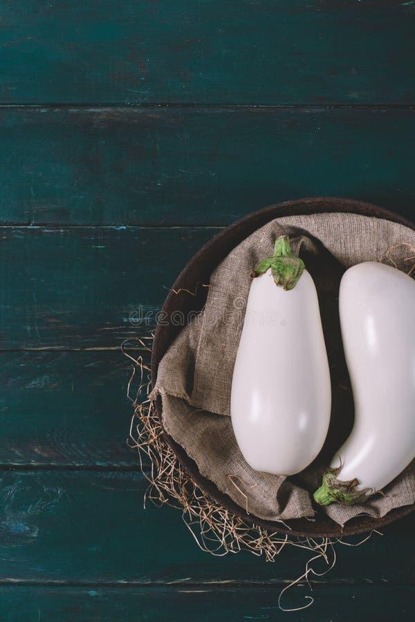 Witte aubergine twee op textiel met droog omhoog gras in een ronde kom op houten spot, uitstekende zwarte ruimteachtergrond van o royalty-vrije stock foto