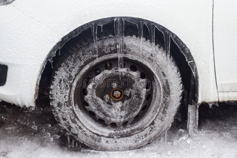 Witte auto met bevroren banden die zich in de winter bevinden stock afbeelding