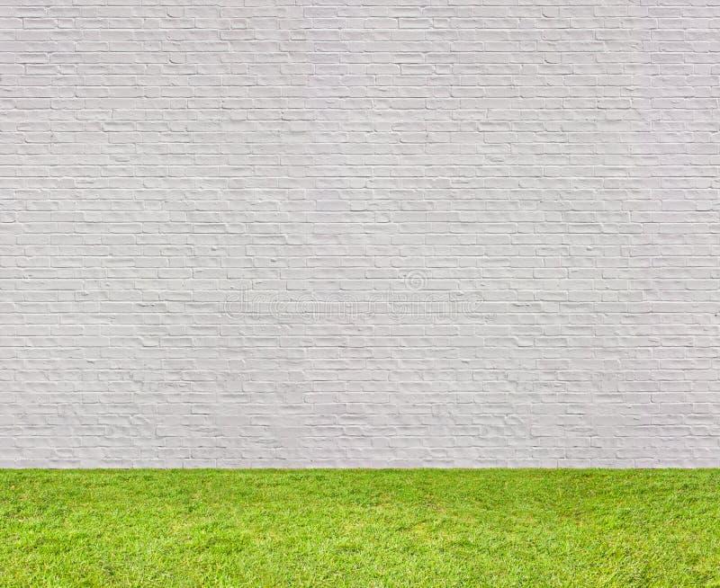 Witte bakstenen muur horizontale naadloos met gazon stock foto's