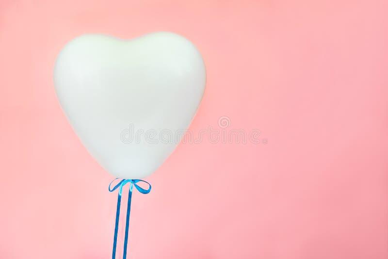 Witte ballon in vorm van hart op koraal roze achtergrond Liefde, valentijnskaart` s dag, verhoudingenconcept royalty-vrije stock afbeelding
