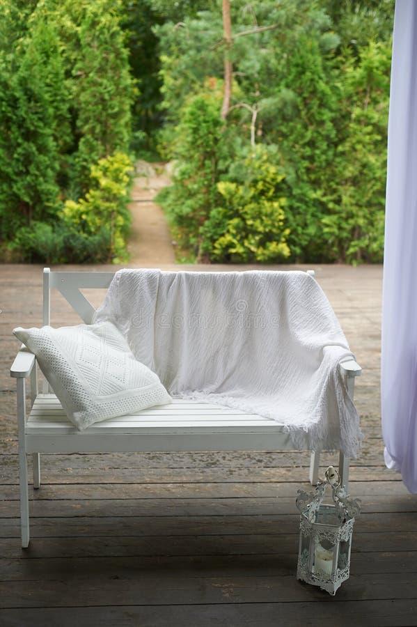 Witte bank op het openluchtterras met houten vloer Achter de tuin Op de bank is een deken en een hoofdkussen Comfortabel royalty-vrije stock afbeelding