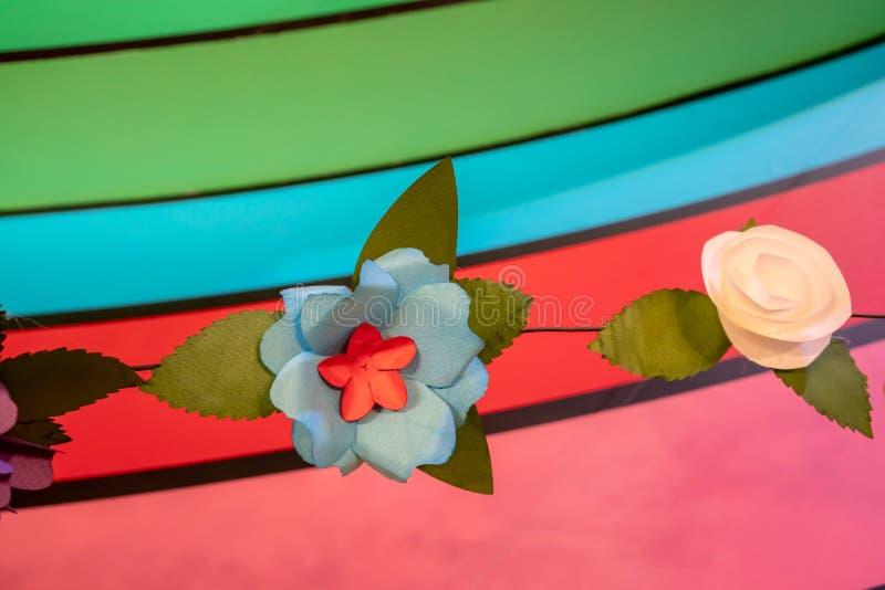 Witte, blauwe en rode document bloemen tegen regenboogachtergrond royalty-vrije stock foto