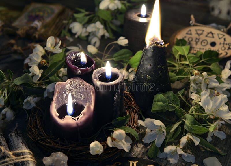 Witte bloemen, zwarte kaarsen en mysticusvoorwerpen stock afbeelding