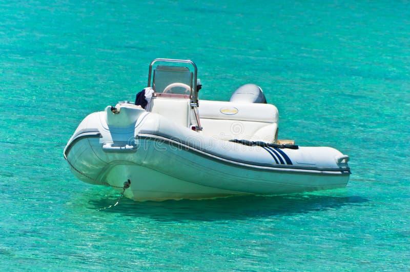 Witte boot bij smaragdgroen zeewater dichtbij klein verlaten eiland in Sithonia stock foto's