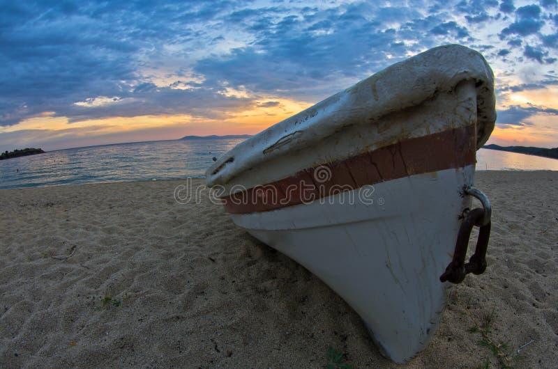 Witte boot op een zandig strand bij zonsondergang, westkust van Sithonia stock foto's