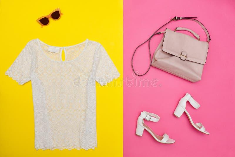 Witte bovenkant, handtas, witte schoenen en roze-gekleurde glazen Helder roze-geel, achtergrond, close-up royalty-vrije stock fotografie