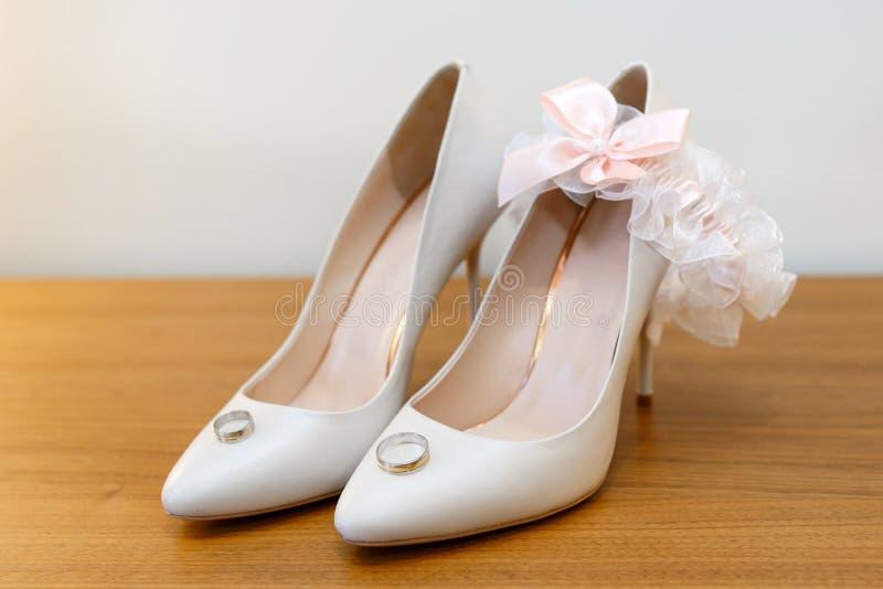 Witte bruid` s schoenen, kouseband en trouwringen stock fotografie