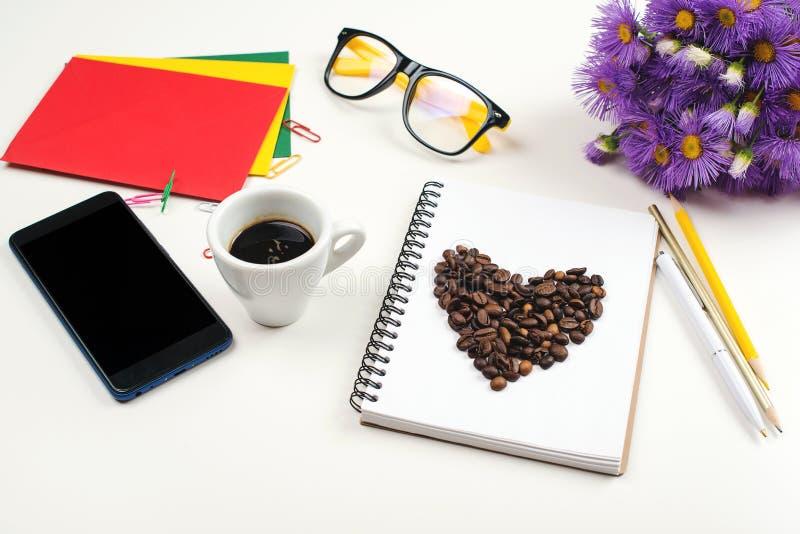 Witte bureaulijst met notitieboekje, pen, glazen, kop van verse espresso De lentebloemen en mobiele telefoon bij lijst royalty-vrije stock foto