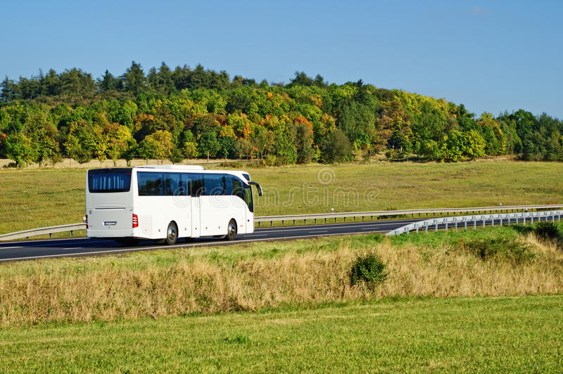 Witte bus op de weg in het platteland stock fotografie
