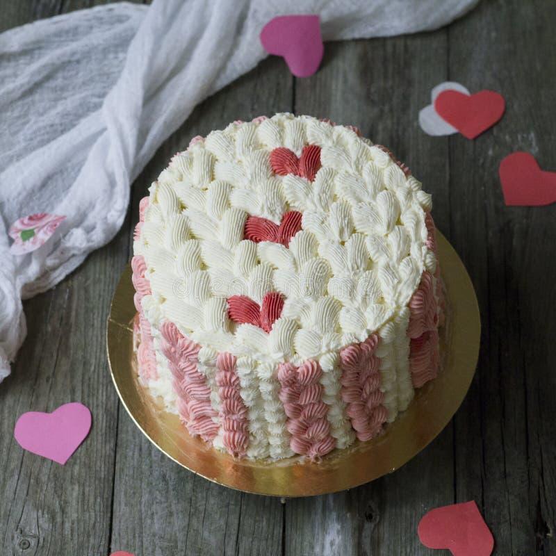 Witte cake met rood roomhart op houten achtergrond met kantstof Het effect van een gebreide oppervlakte op de cake Rood nam toe stock afbeeldingen