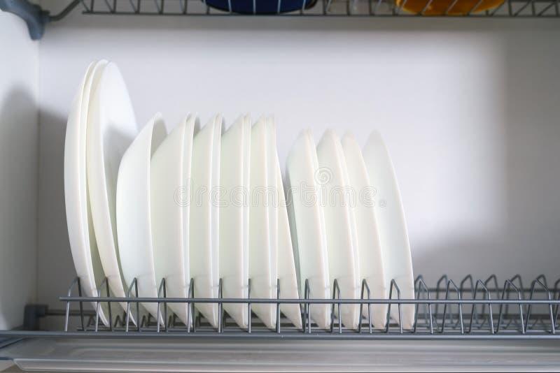 Witte ceramische die platen op een rij in een het drogen kastclose-up worden gestapeld stock foto's