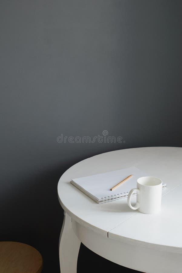 Witte ceramische koffiekop met blocnote en potlood op witte houten lijst in Skandinavisch keukenbinnenland royalty-vrije stock fotografie