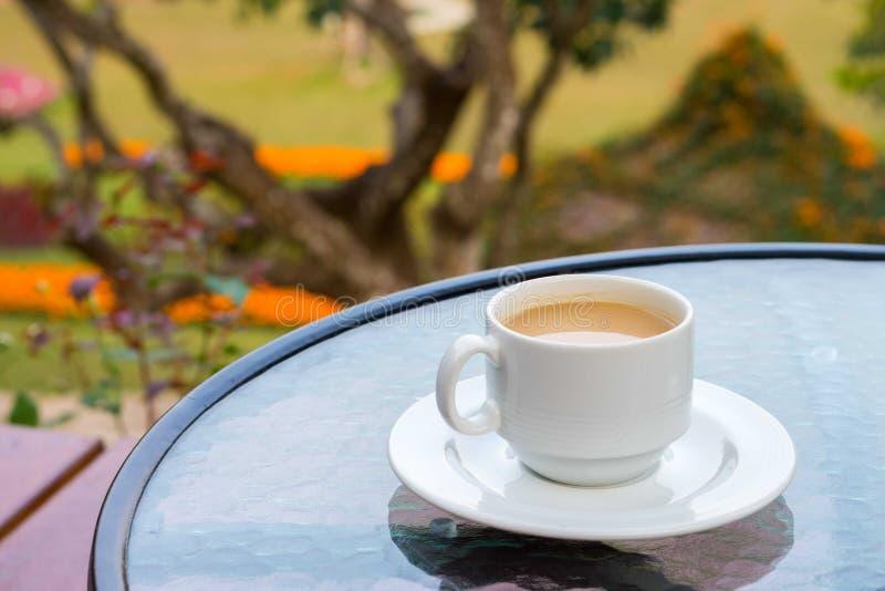 Witte ceramische kop van koffie op glaslijst in binnenplaats stock foto's