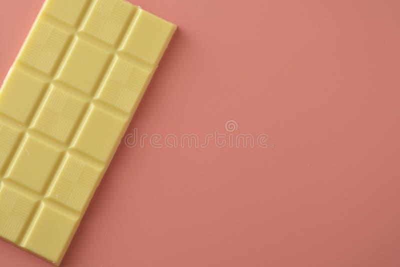 Witte chocolade die over roze achtergrond wordt geïsoleerd De ruimte van het exemplaar stock afbeelding