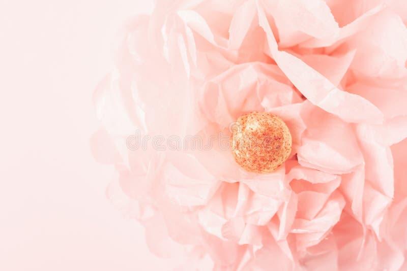 Witte chocolade om suikergoed op een gevoelige roze koraalachtergrond in de vorm van een document bloem De ruimte van het exempla royalty-vrije stock foto