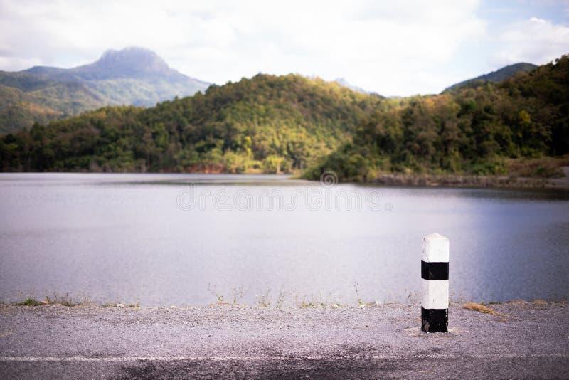 Witte concrete kilometersteen op de binnenweg, een reservoir en een bergketen in Thailand royalty-vrije stock afbeelding