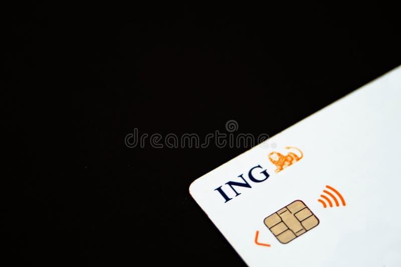 Witte creditcard op duidelijke zwarte achtergrond met het embleem van ING stock afbeeldingen