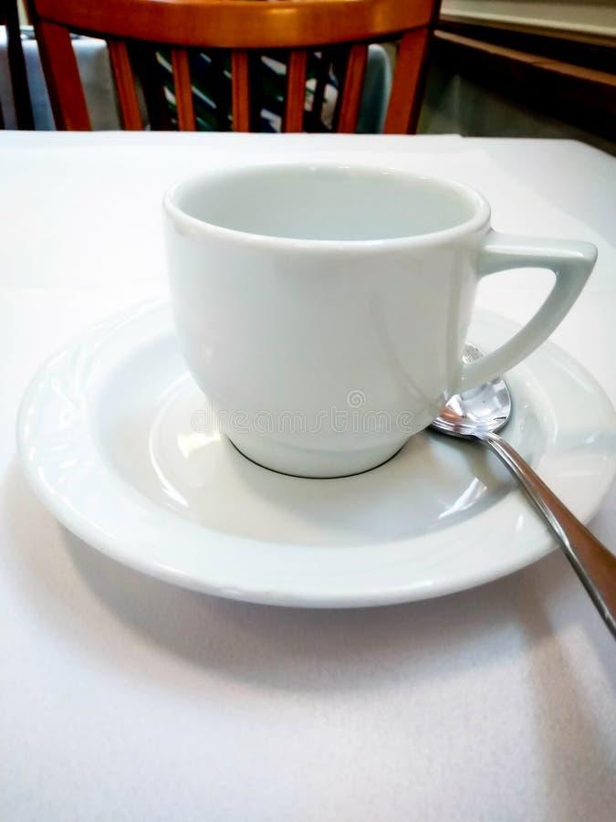 Witte de kop en de schoteltribunes van het koffieporselein op een lijst royalty-vrije stock afbeeldingen