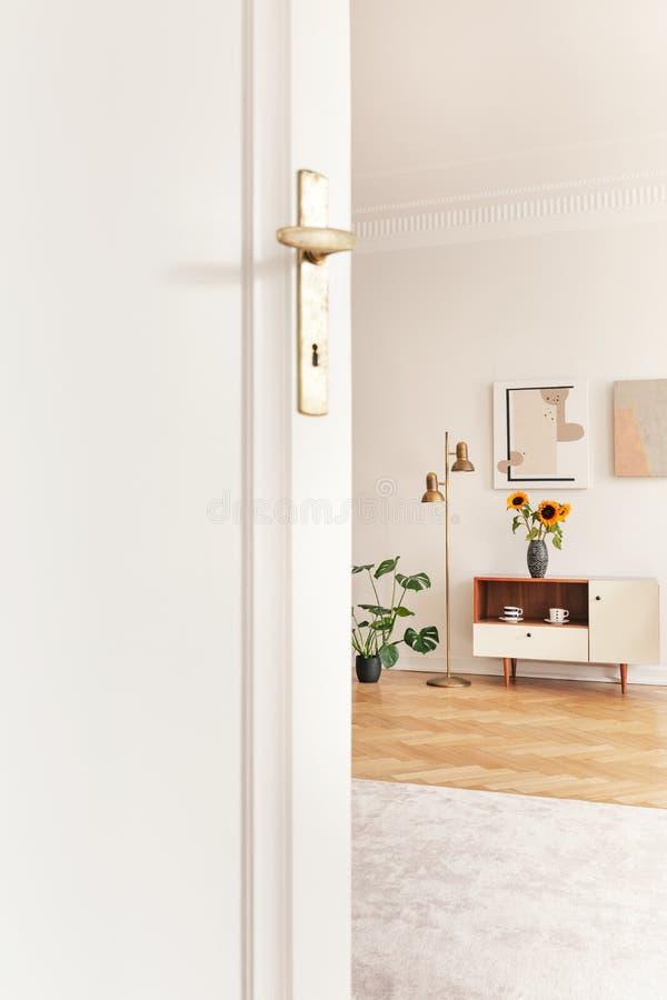 Witte deur in helder woonkamerbinnenland met zonnebloemen op kast op houten vloer Echte foto royalty-vrije stock fotografie