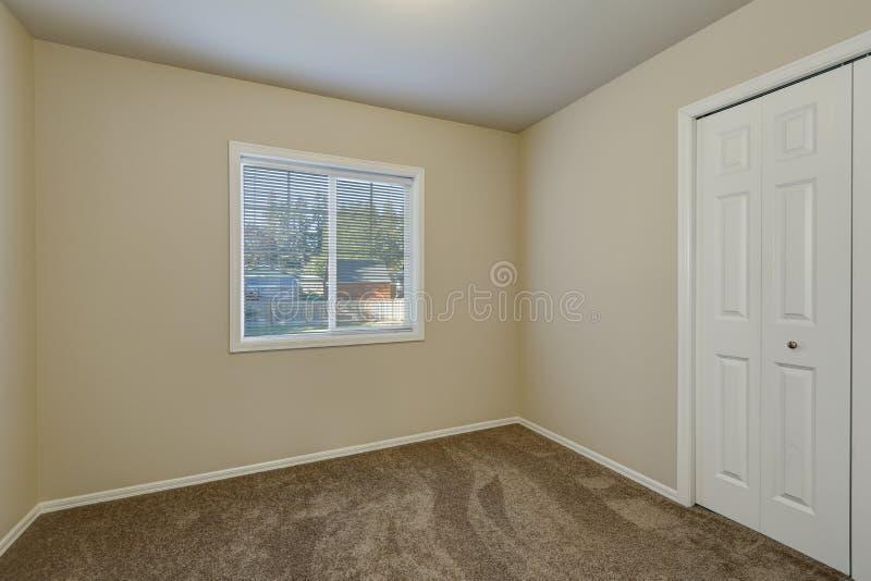 Witte deurenkast en een venster in lege beige ruimte royalty-vrije stock afbeeldingen