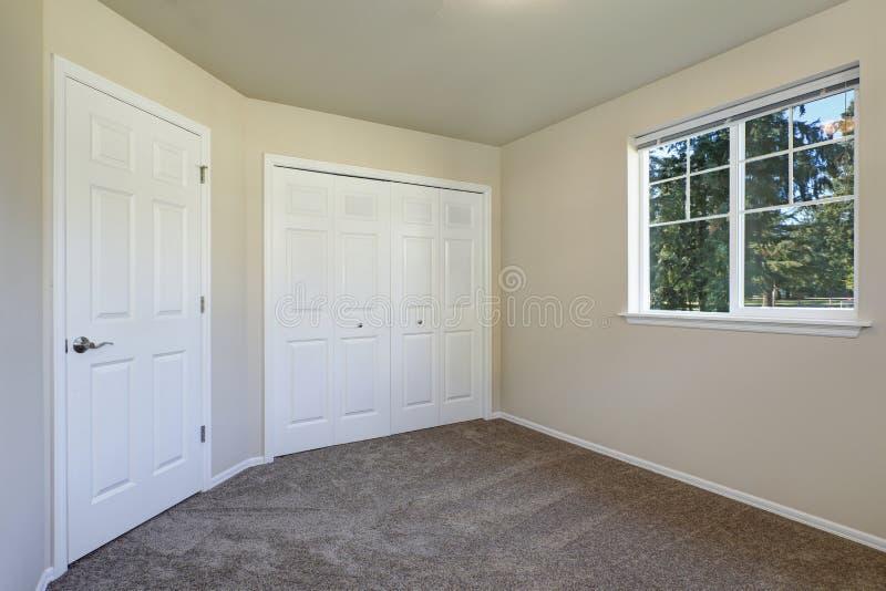Witte deurenkast en een venster in lege beige ruimte royalty-vrije stock fotografie