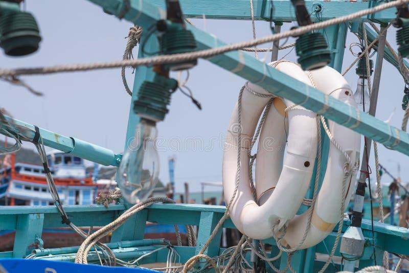 witte die het levensring tegen groene muntpool wordt gehangen van houten vissersboot stock afbeeldingen