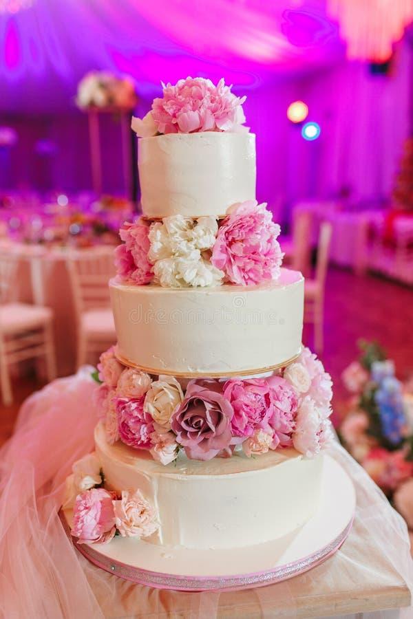 Witte die huwelijkscake met pioenrozen wordt verfraaid op roze restaurantachtergrond stock fotografie