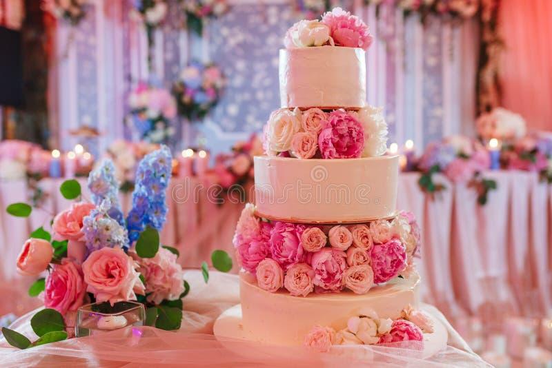 Witte die huwelijkscake met pioenrozen wordt verfraaid op roze restaurantachtergrond royalty-vrije stock afbeeldingen