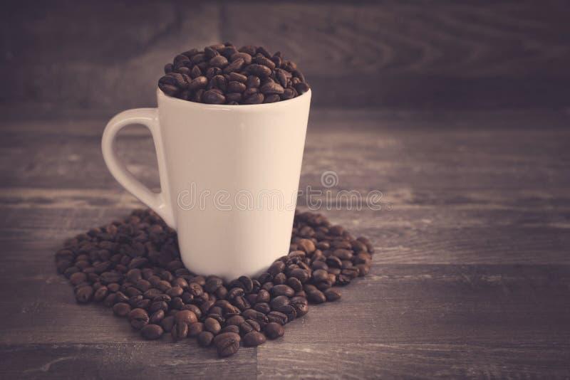 Witte die kop met koffie wordt gevuld bens royalty-vrije stock afbeeldingen