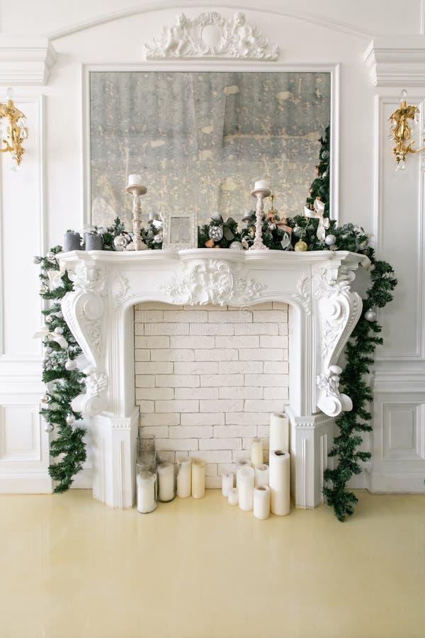 Witte die open haard met kaarsen en spartakken wordt verfraaid Verfraaide Kerstboom Klassieke flats, ochtend in hotel stock fotografie